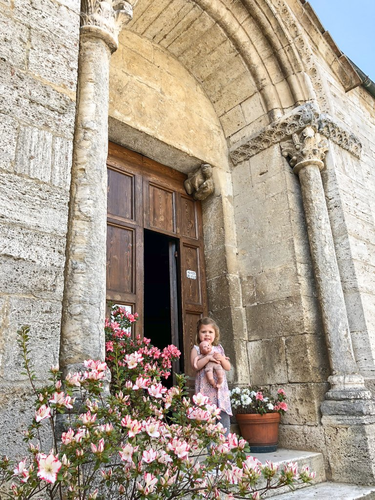 outside a church in San Quirico : Italy with kids