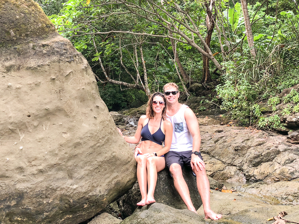 couple sitting on large boulder in the jungle