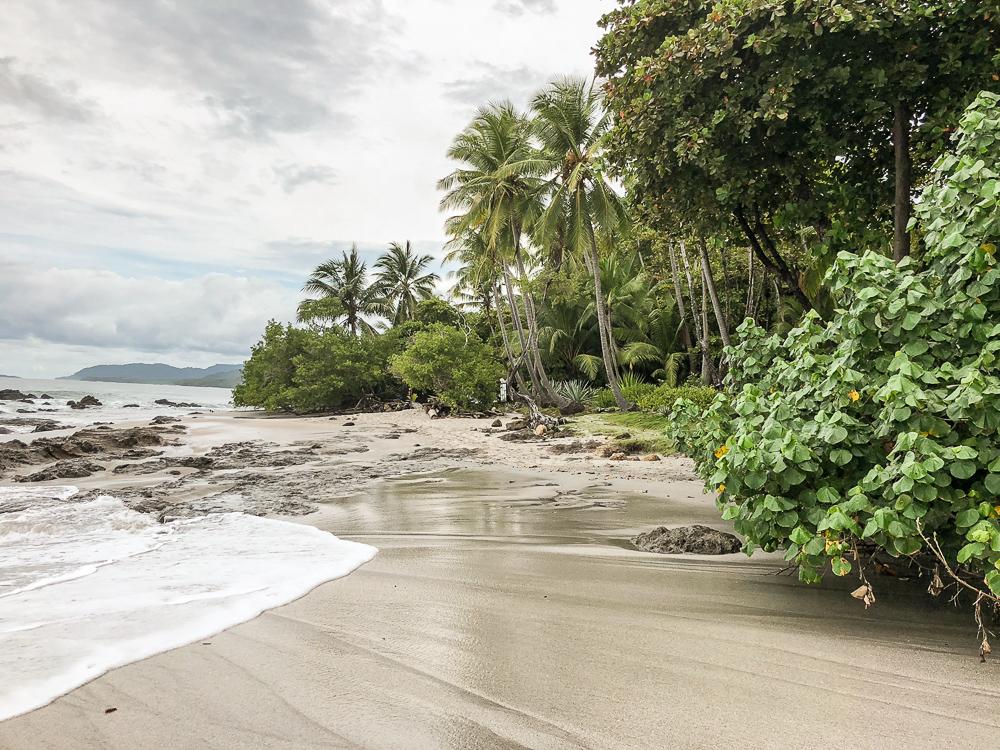 Piedra Colorada sandy beach with large rocks and jungle surrounding