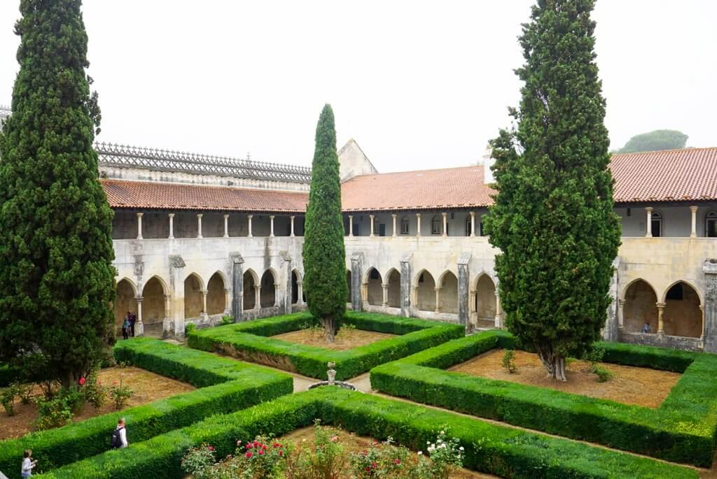 looking down over a cloister with green hedges inside Batalha Monastery