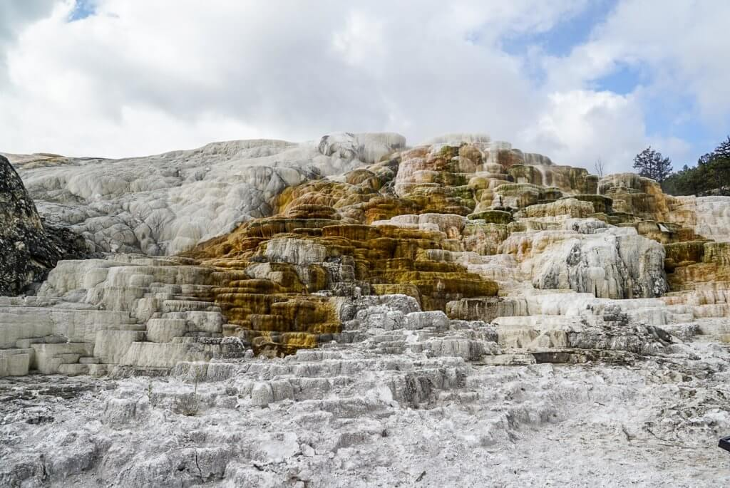 rock formations at Mammoth Springs covered in white and brown mineral deposits